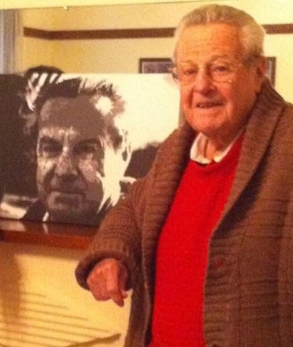 Ray in 2012 with a painting done by his grand-daughter Clare Cook of a younger Ray