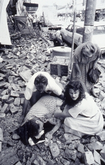 Ladies help an Injured woman in the rubble