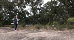 Nicholas Barham launches drone with Dr Greg Blyton in distance